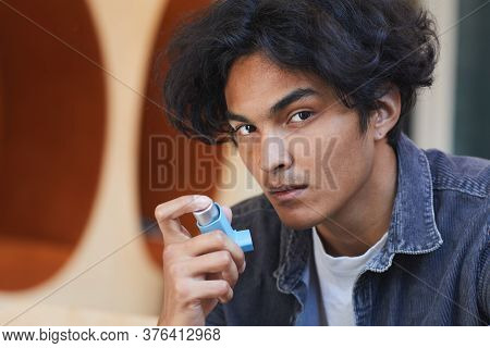 Portrait Of Mixed Race Boy Suffering From Asthma Using Inhaler During Asthma Attack At University