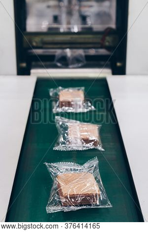 Crispy Wafer Biscuits Packing In The Plastic Back In Production Line On The Conveyor Belt Of Automat