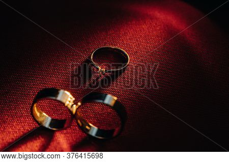 Two Wedding Rings And One Engagement Ring On A Red Background. Three Gold Rings Of A Couple In Love.
