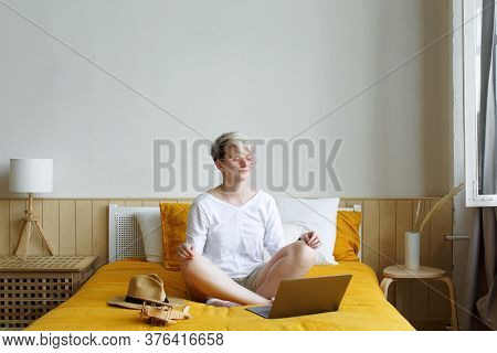 Blonde Bright Hipster Young Woman Meditating Online Sitting On A Bed In Front Of Laptop During Daybr