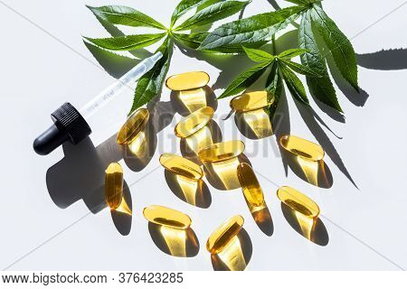 Gelatin Softgels Of Linseed And Flaxseed Oil With Green Leaves. Organic Dietary Supplement. Concept