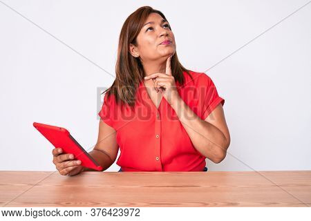 Middle age brunette hispanic woman using touchpad sitting on the table serious face thinking about question with hand on chin, thoughtful about confusing idea