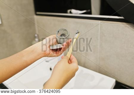 Woman Using Bamboo Toothbrush And Charcoal Toothpaste From Glass Jar For Daily Cleaning Routine. Rec
