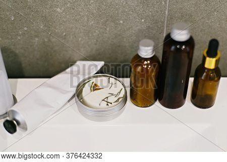 Ubtan For Skin In Glass Bottle, Solid Shampoo In Metal Can, Tonic,  Conditioner On White Sink In Mod
