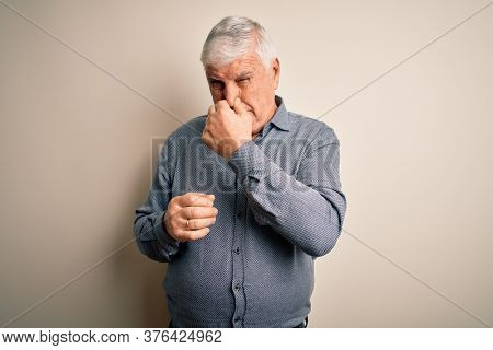 Senior handsome hoary man wearing casual shirt standing over isolated white background smelling something stinky and disgusting, intolerable smell, holding breath with fingers on nose. Bad smell