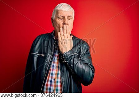 Senior handsome hoary man wearing casual shirt and jacket over isolated red background bored yawning tired covering mouth with hand. Restless and sleepiness.