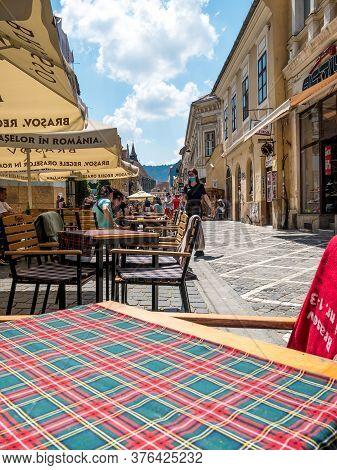 Brasov/romania - 06.28.2020: Walking Street In The Old Town Of Brasov. Outdoor Restaurants And Terra