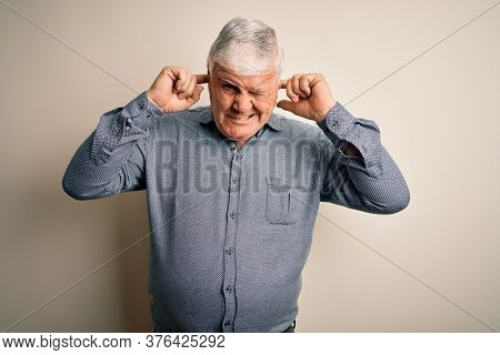 Senior handsome hoary man wearing casual shirt standing over isolated white background covering ears with fingers with annoyed expression for the noise of loud music. Deaf concept.