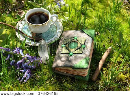 Still Life With Decorated Book Of Tales And Cup Of Tea On The Moss In The Garden. Esoteric, Gothic A