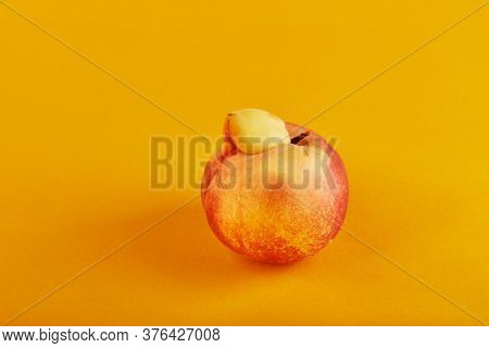 An Ugly Fruit Or Vegetable. Very Ugly Peach Mutant On An Orange Background. Ugly Fruits Are Not In H