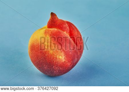 An Ugly Fruit Or Vegetable. Very Ugly Peach Mutant On Blue Background. Ugly Fruits Are Not In High D