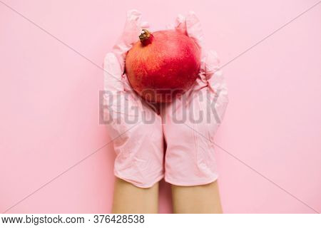 Hands In Pink Glove Holding Pomegranate On Pink Background Flat Lay. Safe Shopping In Quarantine. Or
