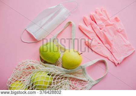 Pink Gloves, Face Mask And Tote Bag With Fresh Apples On Pink Background Flat Lay. Stay Safe. Preven