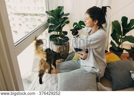 Stay Home Stay Safe. Hipster Girl Hugging And Playing With Two Cats In Modern Room, Sitting Together