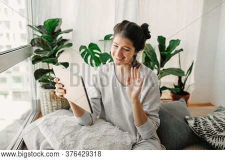 Happy Hipster Girl Chatting On Tablet, Communicating Live With Family  From Home During Quarantine.