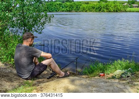 A Fisherman Catches Fish Sitting On The Shore, Against The Backdrop Of A Rural Landscape With A Rive
