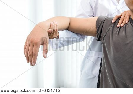 Female Physiotherapists Provide Assistance To Male Patients With Elbow Injuries To Examine Patients