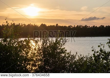Panorama Of A Gorgeous Sunset At A Forest Lake, With Gold And Blue Color In The Sky And Trees Reflec