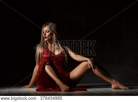 Young Excited Blonde Woman In Sexy Red Shiny Dress With Deep Neckline And Open Legs Sits On Floor Wi
