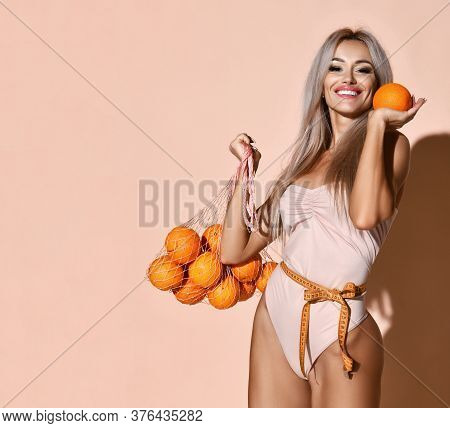 Young Slim Blonde Woman In Swimsuit Stands With Tape Measure On Waist Holding Bag With Oranges Citru