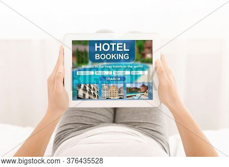 Unrecognizable Girl Booking Hotel Using Tablet Computer Sitting At Home. Accommodation Reservation A