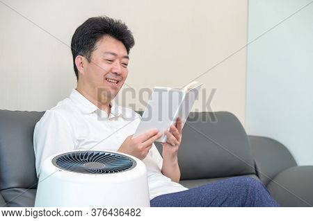 An Asian Middle-aged Man Reading In The Living Room With An Air Purifier On.