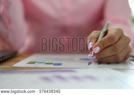 Close-up Of Smart Person Holding Silver Pen For Writing. Important Papers Laying On Working Table. A