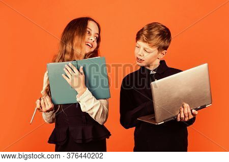 Home Schooling. Little Children Hold Book And Laptop Brown Background. Small Girl And Boy At School.