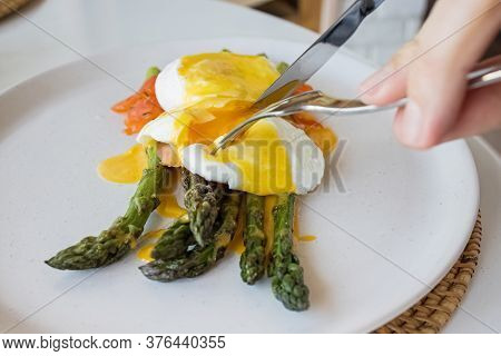 Mans Hands Cutting Poached Egg With Hollandaise Sauce And Salmon Over Asparagus