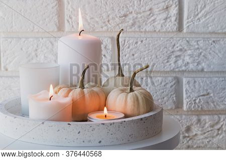 Autumn Home Decor With White Pumpkins And Burning Candles.
