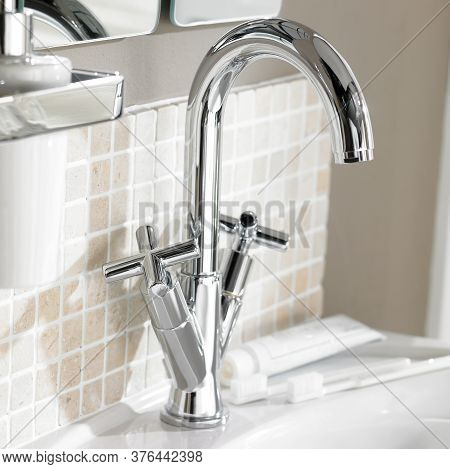 Shot Of Chrome Finish Faucet Set On Washbasin With Tiled Wall