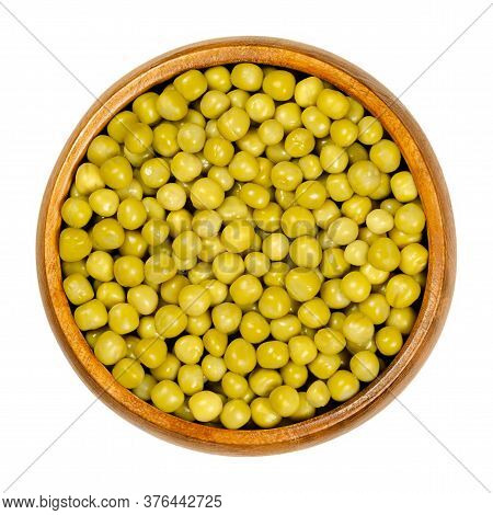 Canned Green Peas In Wooden Bowl. Small Spherical Seeds Of The Pod Fruit Pisum Sativum, Boiled And C