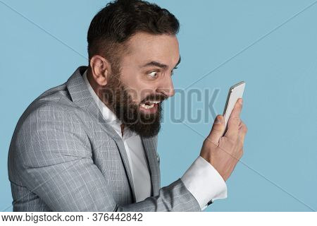 Angry Young Manager Shouting At Smartphone In Fury Over Blue Background