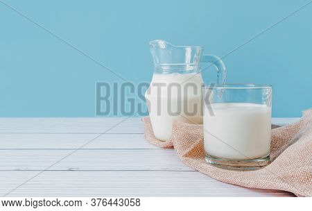 Natural Fresh Milk In A Glass And Pitcher, Placed On A Napkin On A Wooden Table On A Blue Background