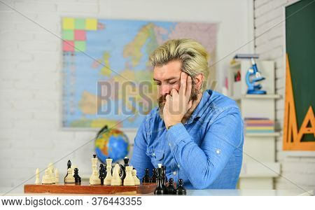 Chess Academy. Focused School Teacher. Thinking Of Attacking And Capturing Opponent Chess Pieces. Th