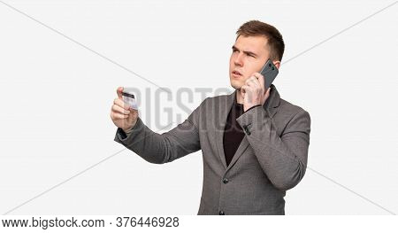 Bank Fraud. Scam Call. Doubtful Business Man With Credit Card Talking On Phone Isolated On White Bac