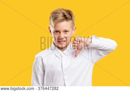 Dislike Gesture. Failure Disgust. Annoyed Boy In White Shirt Showing Thumb Down Isolated On Yellow B