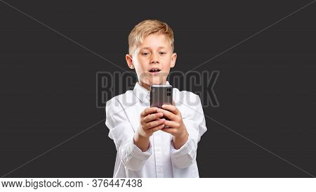 Online Chat. Mobile App. Amazed Boy In White Shirt Reading Message On Smartphone Isolated On Dark Ba