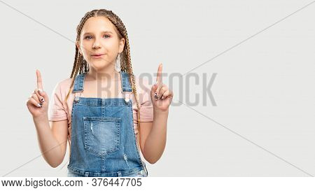 Amazed Child Portrait. Ad Background. Surprised Girl Isolated Pointing Up At White Copy Space.