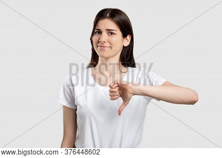 Dislike Gesture. Bad Idea. Disappointed Woman Showing Thumb Down Isolated On Light Background.