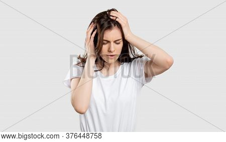 Suffering Woman Portrait. Migraine Pain. Stressed Out Lady Touching Head Isolated On Neutral Backgro