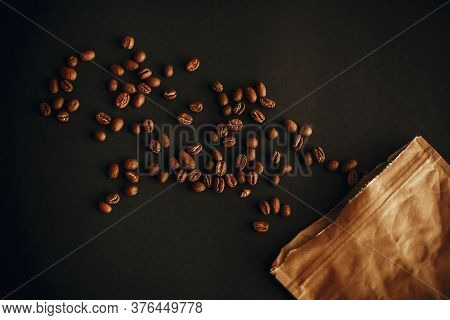 Coffee Beans Scattered From Paper Pack On Black Background Flat Lay. Fresh Aromatic Roasted Coffee B