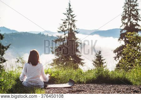 Young Woman Practicing Yoga And Sitting In Lotus Position On Top Of Mountain Among Grass In Sunny Mo