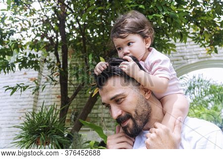Cheerful Father Holding And Piggyback His Baby Daughter In His Neck While Relax Time At Home. Enjoym