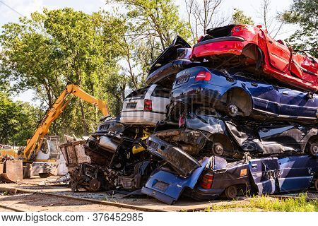 Graz, Austria - 24.06.2020 - Cars Piled On Top Of Each Other In Junkyard