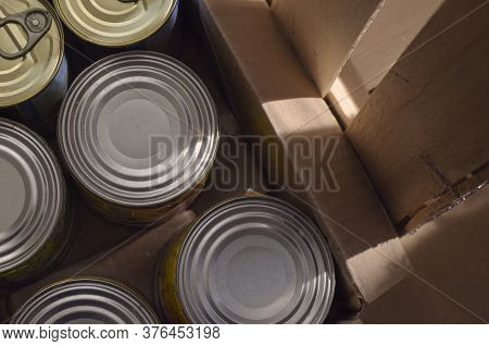 Tin Cans In A Cardboard Box. Variety Of Canned Food In Full Tin Cans. Real Canned Food. View From Ab