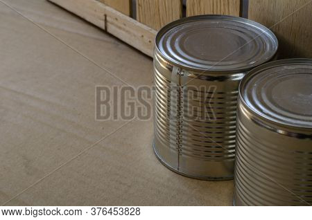 Two Cans Of Canned Food Next To A Wooden Box. Close-up Of Canned Food For Long-term Storage. Canned