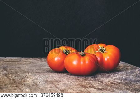 Three Organic Red Tomatoes On A Wooden Table On A Black Background. Healthy Eating.