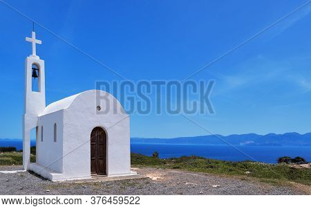 White Greek Orthodox Chapel Or Church On Hilltop Of Seashore Against Clear Blue Sky On Sunny Day.