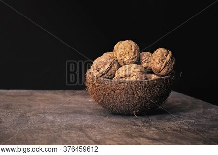Group Of Shelled Walnuts In A Coconut Shell Bowl On A Wooden Table On Black Background. Healthy Eati
